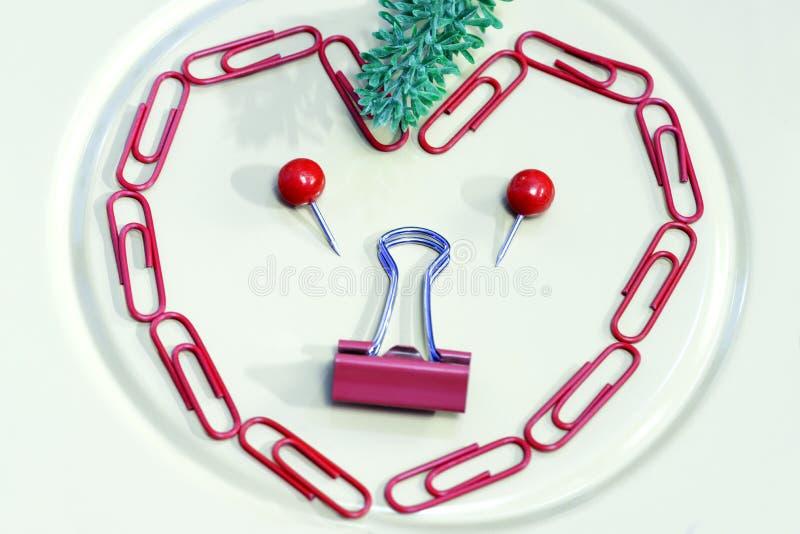 Stående som St-Valentin's illustreras av den kontorshäftstift och musslan royaltyfri bild