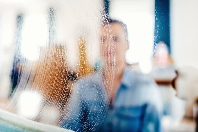 stående suddiga ut detaljer av fönsterlokalvård Tvåltvättmedel och torkduk på fönsterexponeringsglas royaltyfria bilder