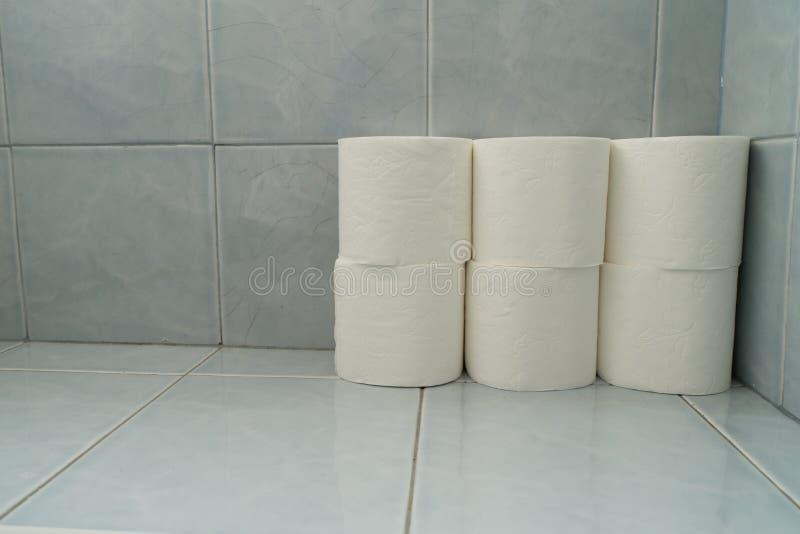 Stående toalettpapper Extra rullar på ett blått belagt med tegel golv i bakgrund för rent hygieniskt hem för husbadrumvägg kompak royaltyfri foto