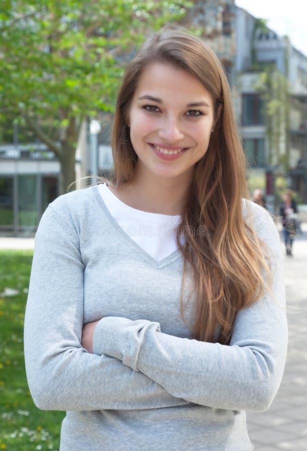 Stående ung kvinna med korsade armar i tillfällig kläder utanför arkivfoto
