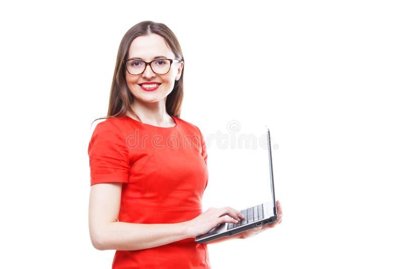 Stående ung vuxen kvinna i den röda klänningen & exponeringsglas som rymmer bärbar datordator - I arkivbild