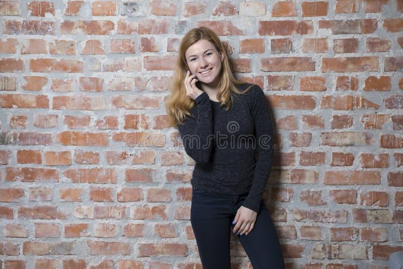 Stående yttersida för ung kvinna mot tegelstenväggen på solig dag, genom att använda hennes smarta telefon fotografering för bildbyråer