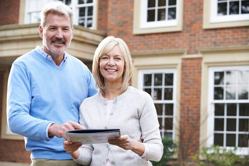 Stående yttersidahus för mogna par som ser egenskapsdetaljer arkivfoton