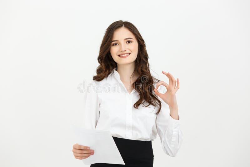 Ståendeaffärskvinna som visar reko le för handtecken som är lyckligt Ung nätt Caucasian affärskvinna på vit royaltyfri foto