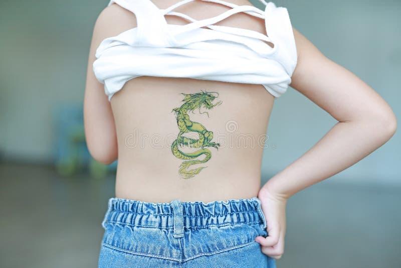Ståendebaksida av lilla flickan med draketatueringklistermärken på hennes hud Klä upp tatueringar arkivbild