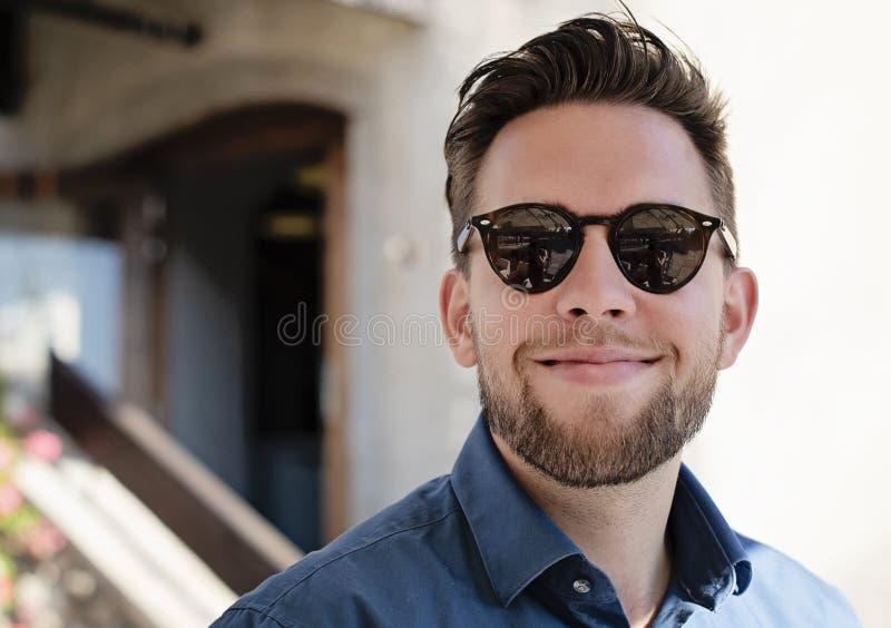 Ståendebild av den unga stiliga mannen med att le för exponeringsglas royaltyfria foton