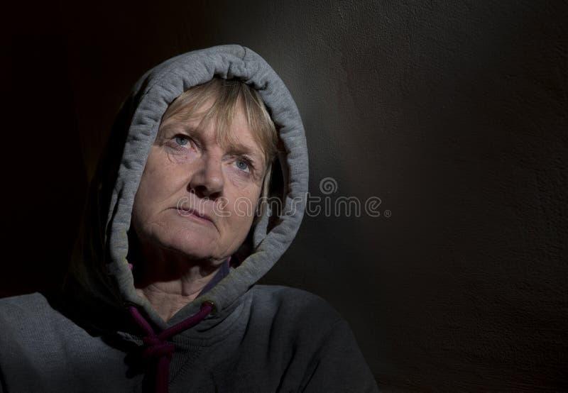 Ståendebild av en deprimerad mogen kvinna i ett mörkt rum royaltyfria bilder