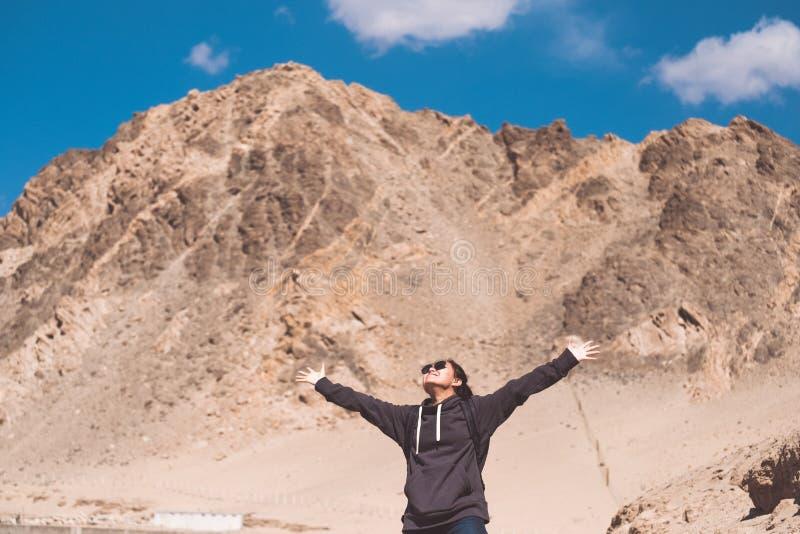 Ståendebild av en härlig asiatisk kvinnaturist som framme sträcker armar och anseende av berget royaltyfria foton