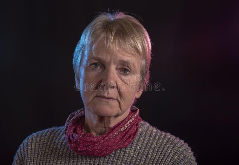 Ståendebild av en mogen kvinna på en svart bakgrund arkivfoton