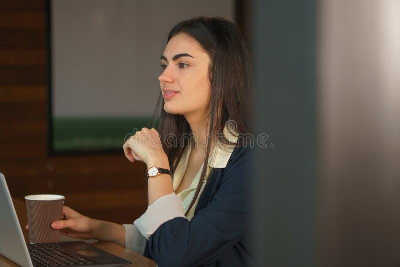 Ståendebrunettflickan med en bärbar dator och ett kaffe tänker, innan han gör ett viktigt beslut arkivbilder