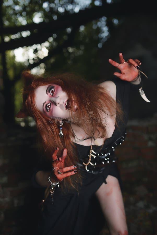 Ståendeflickan med rött hår och blodar ner framsidavampyren, mördaren, psykopaten, det halloween temat, blodig kvinna arkivbild