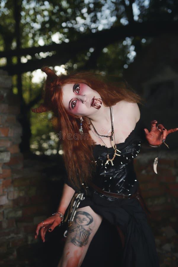 Ståendeflickan med rött hår och blodar ner framsidavampyren, mördaren, psykopaten, det halloween temat, blodig kvinna arkivfoton