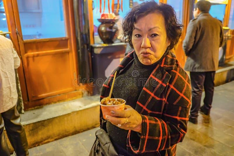 Ståendefoto av den höga asiatiska kvinnaköttbollen i Wangfujing som går gatan och gatamat i den beijing staden, arkivbilder