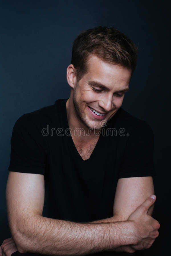 Ståendefoto av den unga lyckliga mannen med ett bländande leende i v-nec royaltyfri fotografi