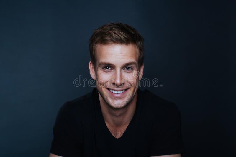 Ståendefoto av den unga lyckliga mannen med ett bländande leende i v-nec arkivfoto