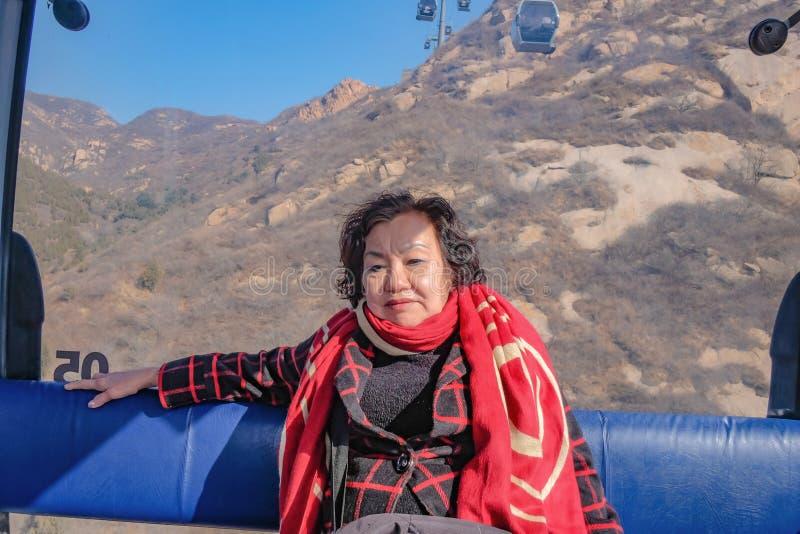 Ståendefotoet av den höga asiatiska kvinnahandelsresanden som sitter på kabelbilen, korsar berget till den stora väggen av Kina royaltyfri foto