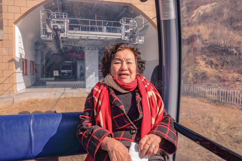 Ståendefotoet av den höga asiatiska kvinnahandelsresanden som sitter på kabelbilen, korsar berget till den stora väggen av Kina p royaltyfri foto