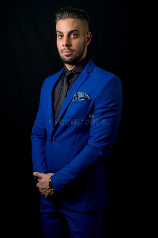 Ståendefotoet med en ung allvarlig man med blått passar royaltyfri fotografi
