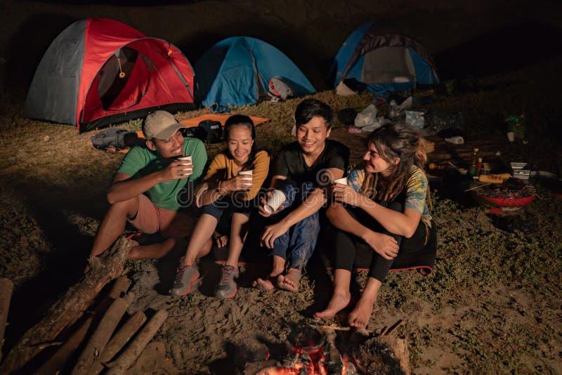 Ståendegrupp av vänner som campar som sitter runt om lägerbrand royaltyfri fotografi
