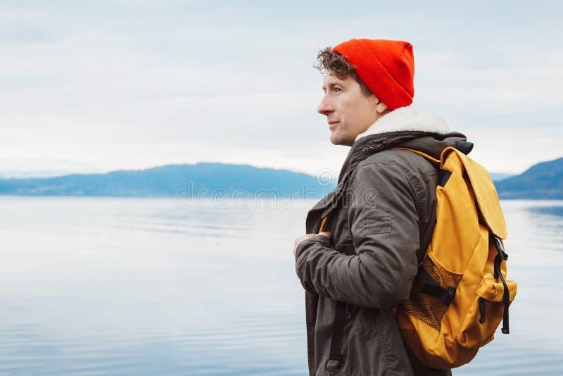 Ståendehandelsresandeman med en gul ryggsäck som bär en röd hatt på kusten på bakgrunden av berget och sjön arkivfoto