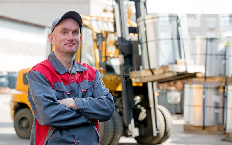 Ståendeindustriarbetare på lagergaffeltruckbakgrund royaltyfri bild
