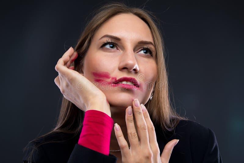 Ståendekvinna med smetad läppstift som ser upp royaltyfria bilder
