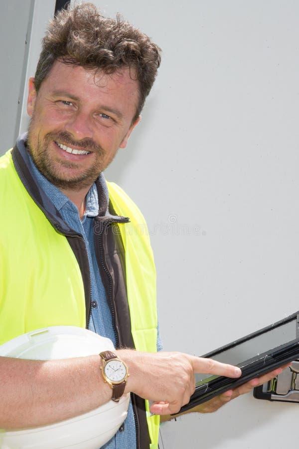 Ståendeleveransman som ler genom att använda den digitala minnestavlan royaltyfria foton