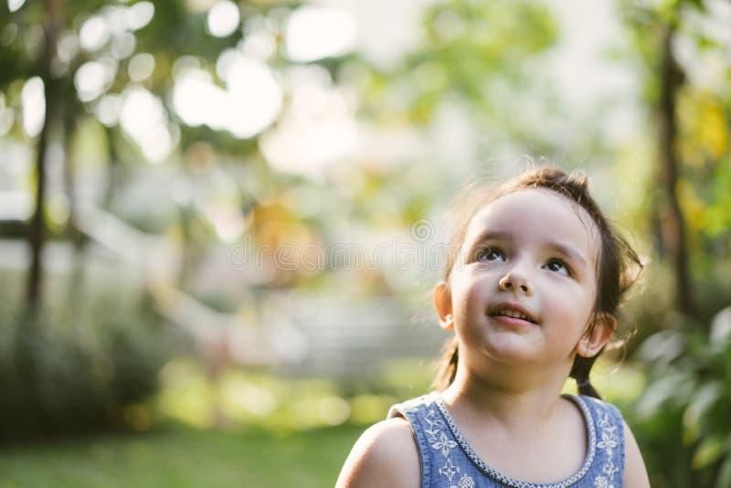 Ståendelilla flickan i natur parkerar gulliga ungar som ser upp arkivbilder