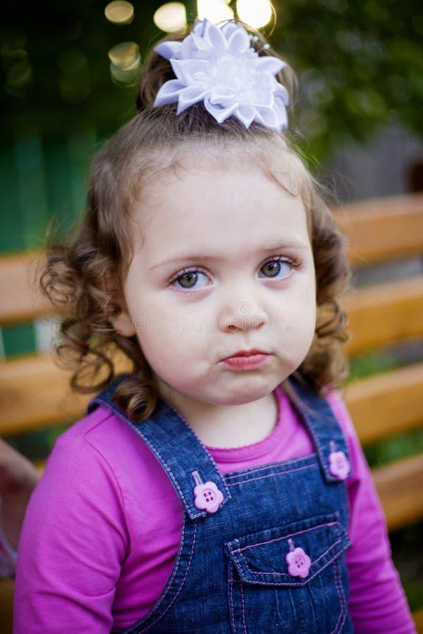 Ståendelilla flickan låtsar ingenting den hända närbilden arkivbilder