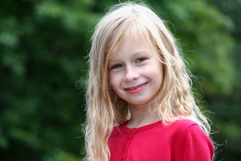 Ståendeliten flicka med långt blont hår i en röd tröja som ler och ser direkt på kameran royaltyfri fotografi