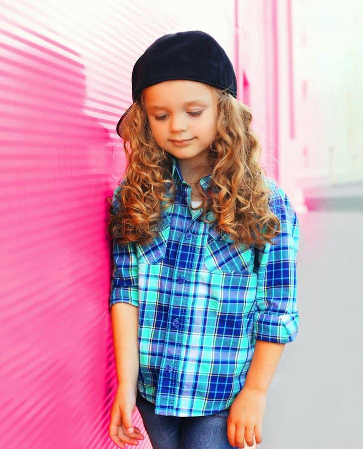 Ståendeliten flickabarn i den rutiga skjortan, baseballmössa arkivbild