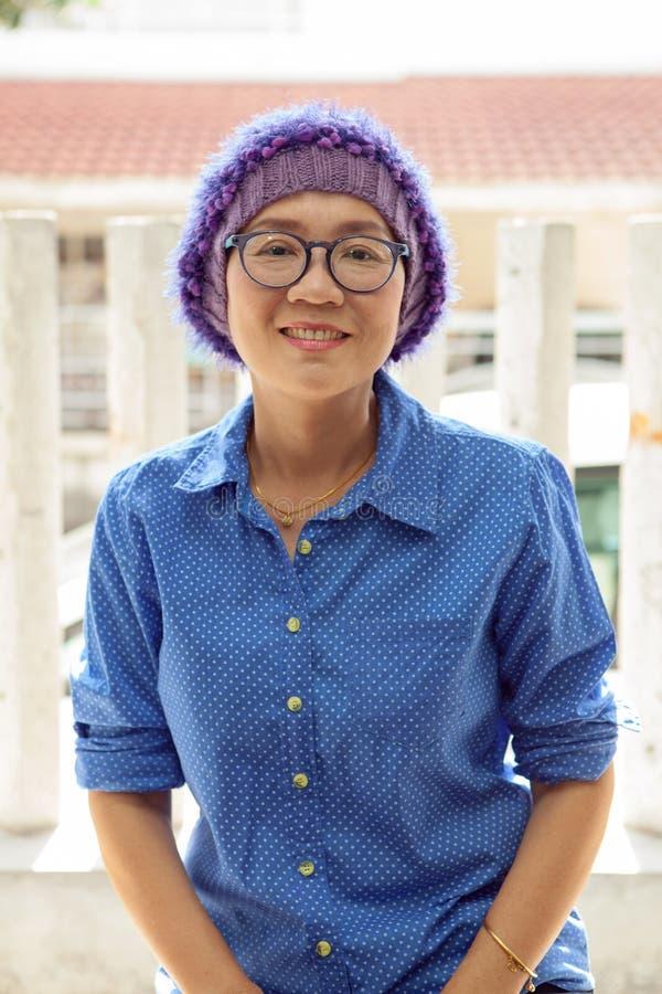 Ståendelyckaframsida av den bärande handarbetehuven för asiatisk kvinna för fotografering för bildbyråer
