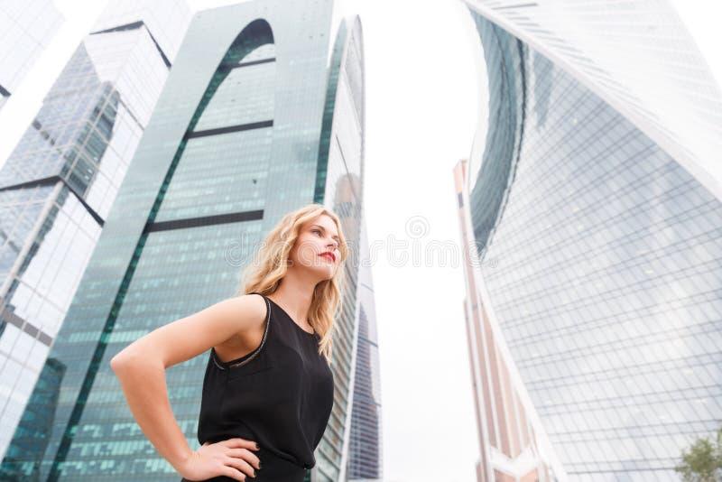 Ståenden av affärskvinnaanseendet i halvt vänder på gatabakgrund fotografering för bildbyråer