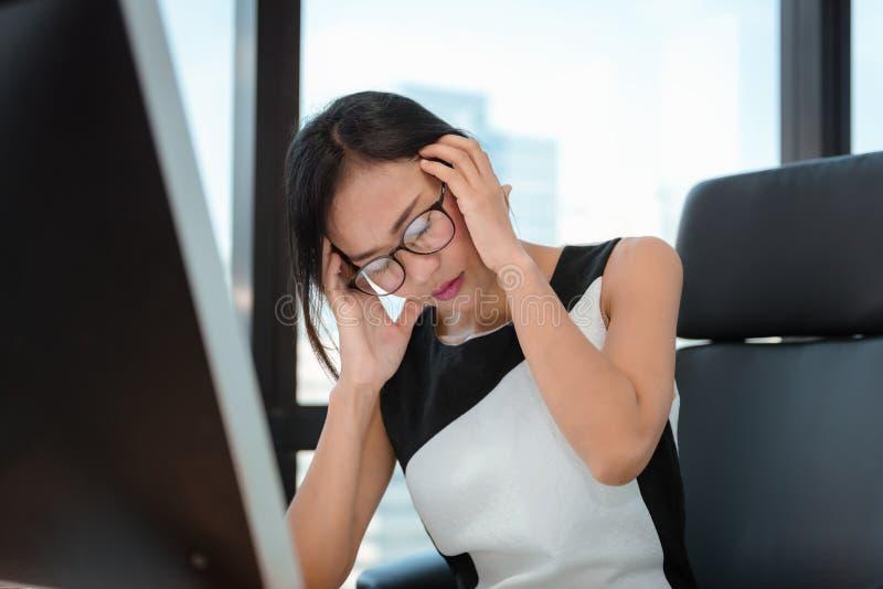 Ståenden av affärskvinnan som har huvudvärk under att arbeta i regeringsställning arbetsplatsen, den asiatiska kvinnan, lider frå arkivfoto