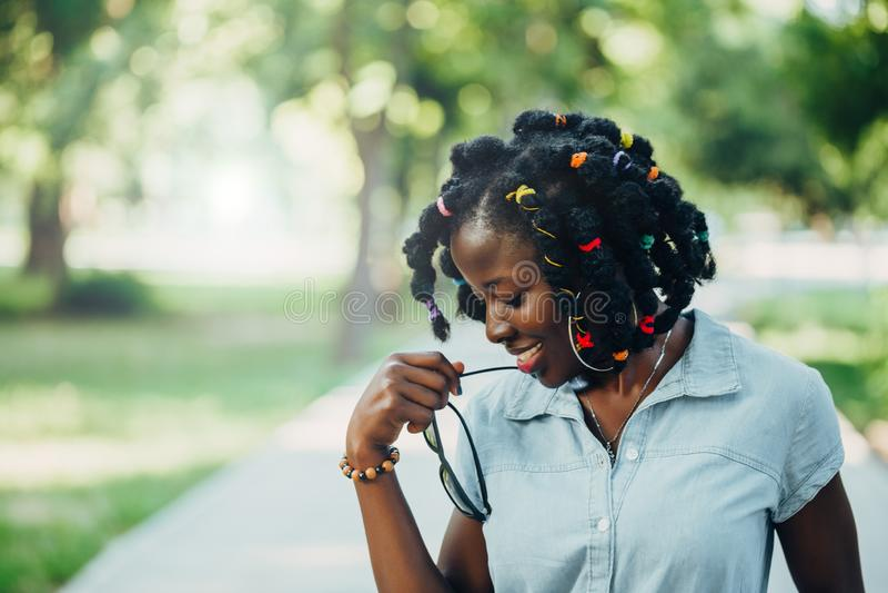 Ståenden av afrikansk skönhet som ler den unga svarta kvinnan med solglasögon i, parkerar med solsignalljuset royaltyfri fotografi