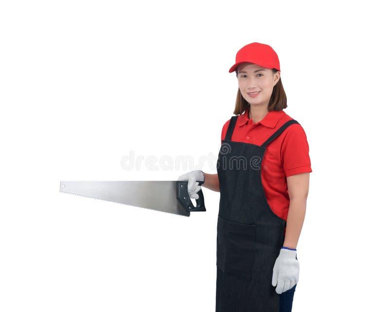 Ståenden av arbetaren för den unga kvinnan som ler i röd likformig med förklädet, handskehandinnehav, såg isolerat på vit backrou royaltyfria bilder