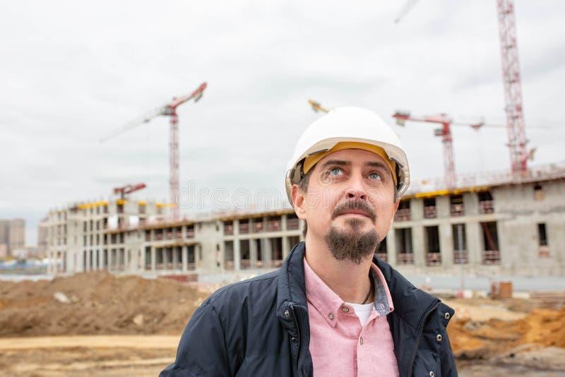 Ståenden av arkitekten på arbete med hjälmen i en konstruktionsplats, läser planet fotografering för bildbyråer