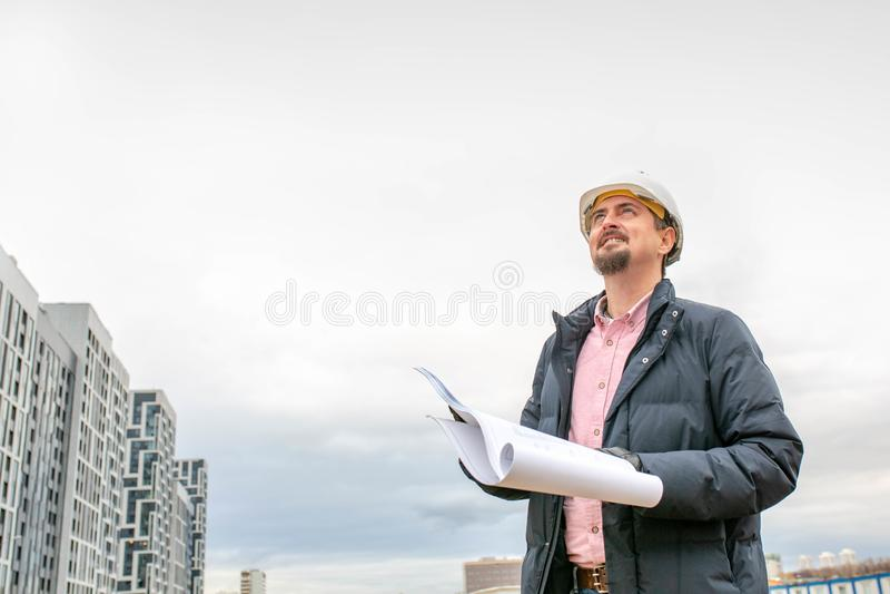Ståenden av arkitekten på arbete med hjälmen i en konstruktionsplats, läser planet arkivbilder