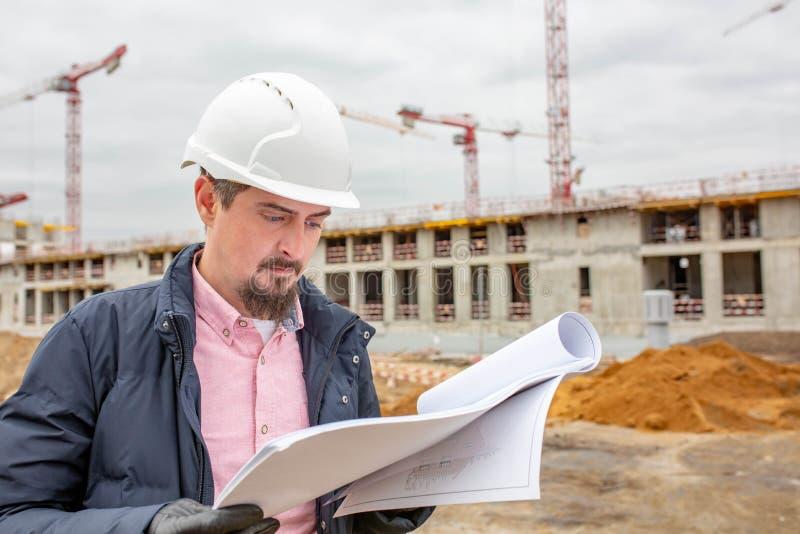 Ståenden av arkitekten på arbete med hjälmen i en konstruktionsplats, läser planet royaltyfri bild