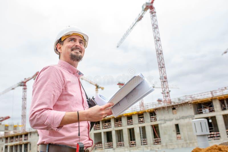 Ståenden av arkitekten på arbete med hjälmen i en konstruktionsplats, läser planet arkivbild