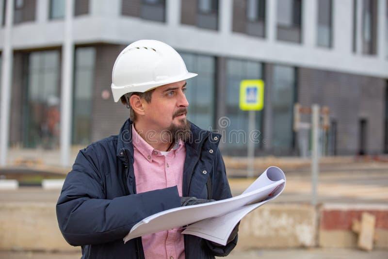 Ståenden av arkitekten på arbete med hjälmen i en konstruktionsplats, läser planet, pappers- projekt arkivfoto