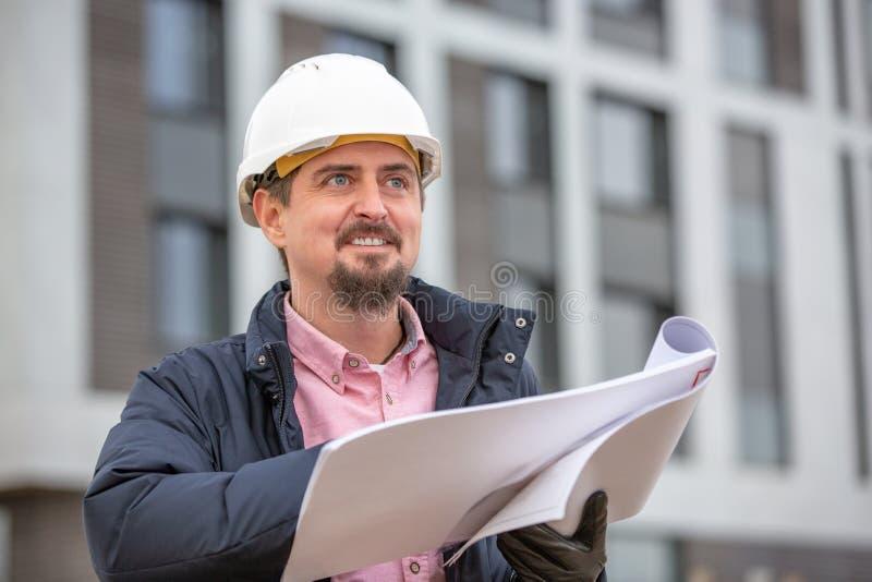 Ståenden av arkitekten på arbete med hjälmen i en konstruktionsplats, läser planet, pappers- projekt fotografering för bildbyråer
