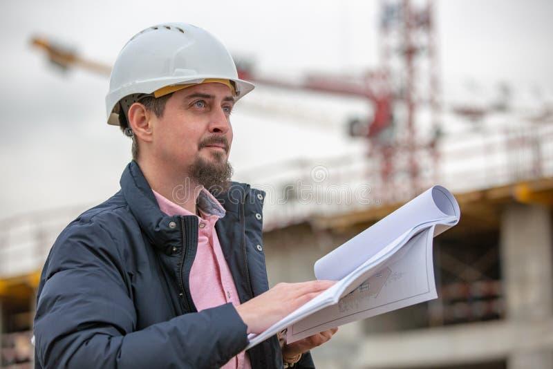 Ståenden av arkitekten på arbete med hjälmen i en konstruktionsplats, läser planet, pappers- projekt royaltyfria bilder