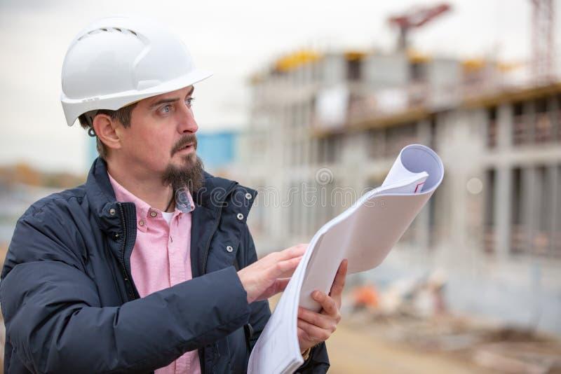 Ståenden av arkitekten på arbete med hjälmen i en konstruktionsplats, läser planet, pappers- projekt arkivbilder