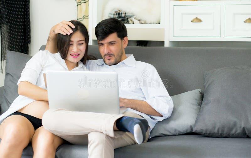 Ståenden av asiatiskt barn kopplar ihop make- och frusammanträde på soffan arkivbild