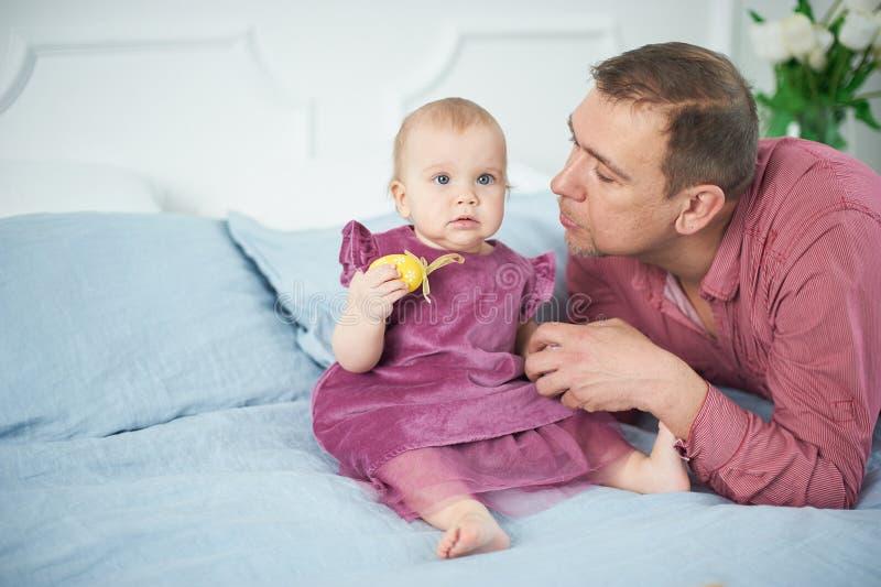 Ståenden av att älska fadern som spelar med hans 10 gamla månader, behandla som ett barn i sovrum arkivfoton