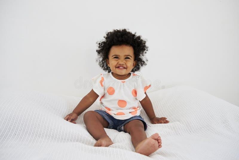 Ståenden av att le behandla som ett barn flickasammanträde på säng fotografering för bildbyråer