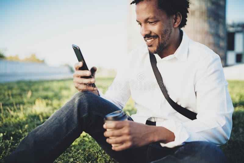 Ståenden av att le den amerikanska afrikanska mannen i headphonen som tar bromsen på soligt, parkerar med kaffe i bort kopp för t royaltyfria bilder
