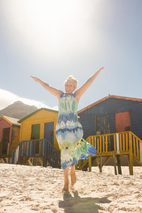Ståenden av att le den höga kvinnan med armar lyftte att gå på sand på stranden arkivfoton