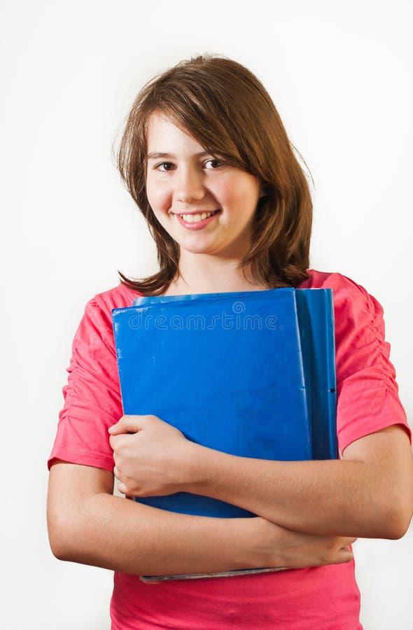 Ståenden av att le den teen flickan rymmer böcker isolerade royaltyfria bilder